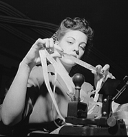 Miss Genie Lee Neal reading a perforated tape at the Western Union telegraph office. Washington, DC. June 1943. FSA/OWI Collection